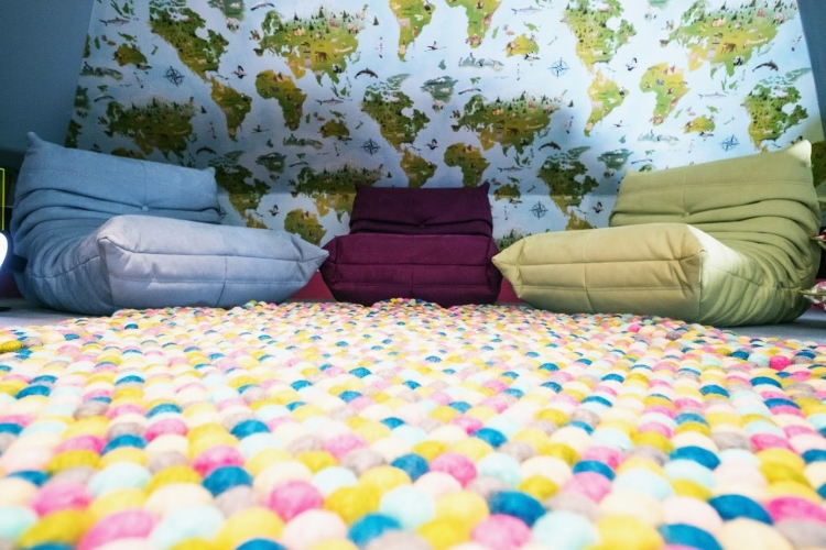 Multicoloured felt ball rug_mini togo_Heals furniture_Ligne Roset_Kids playroom design_world map wall paper_blue and green playroom_MK Kids Interiors_Pom pom rug