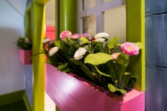 Kids-Playhouse-designer_Wendy-house-design_kids-playroom-design_window-plant-pot_close-up-of-flowers_pink-plant-pot-with-pink-and-white-flowers_pink-green-and-grey-house