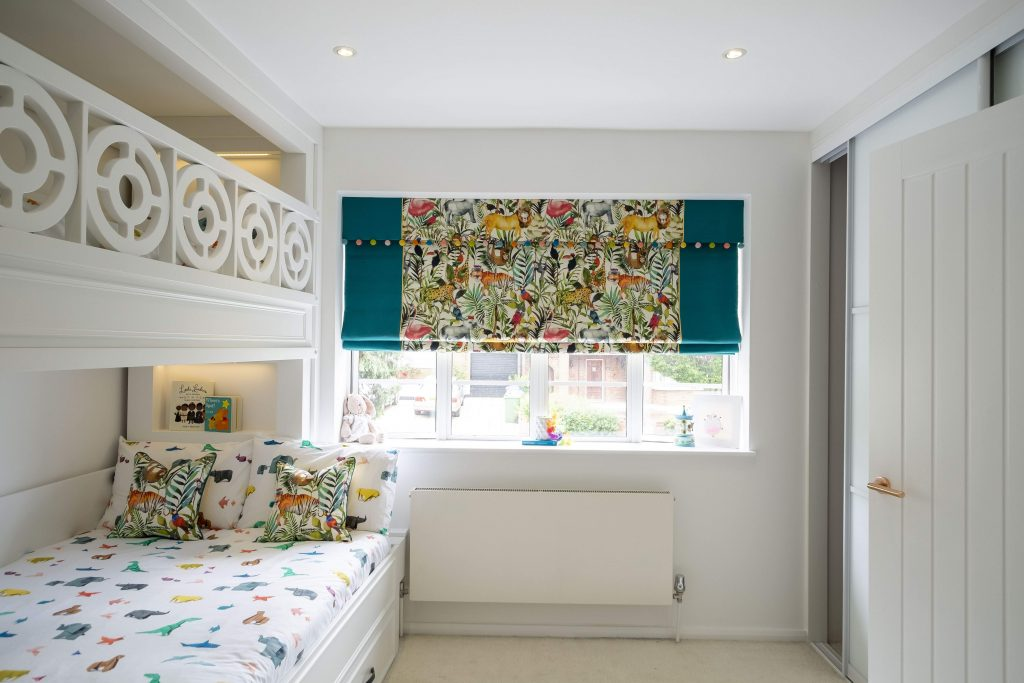 Jungle themed roman blinds with a pom-pom trim- MK Kids Interiors- small double bunk bed with trundle bed and step drawers- London childrens interior designer