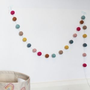 Happy Days Rainbow Pom-pom Garland in light pink, fuchsia pink, mustard, neutral, light blue and dark blue