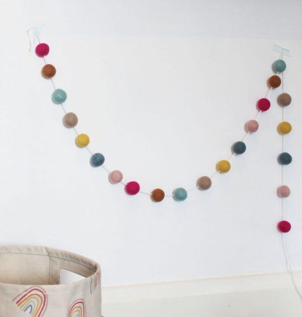 Happy Days Rainbow Pom-pom Garland in light pink, fuchsia pink, mustard, neutral, light blue and dark blue