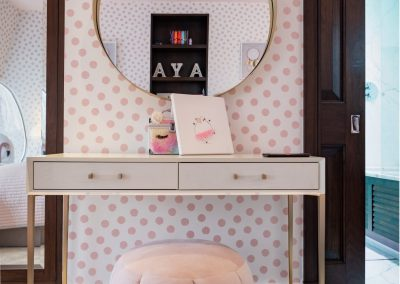 round brass mirror with a two drawer white dresser and pink pouff, egg chiar in the mirror